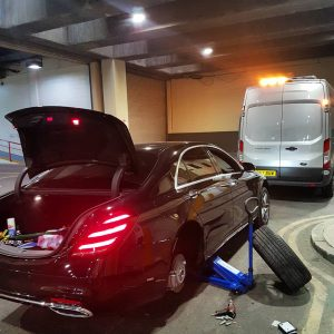 Black Mercedes car stuck indoors with tyre problem